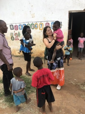 Maria Moreno holding a child from an orphanage school. This is the Create Peace Project Uganda school.