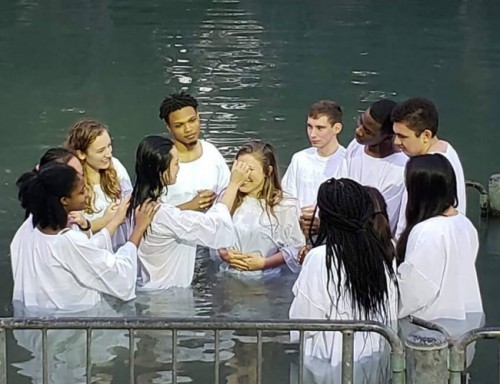 Audrey Novak, in a white robe surrounded by other students from her group also dressed in white robes, stands in the Jordan River to be baptized.