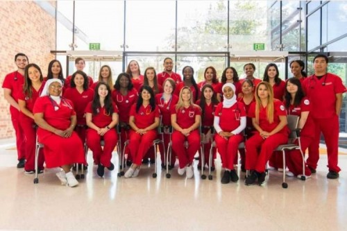 Dressed in red, the graduating class of nurses pose for a group photo.