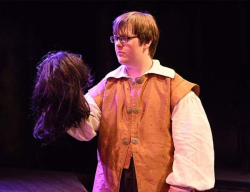 Dylan Smail, wearing glasses and a Renaissance costume, holds a dummy head in a play.