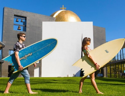 Students walk in front of the Chapel of St. Basil while holding surfboards.