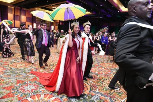 Mardi Gras Queen and King lead the procession holding parasols.