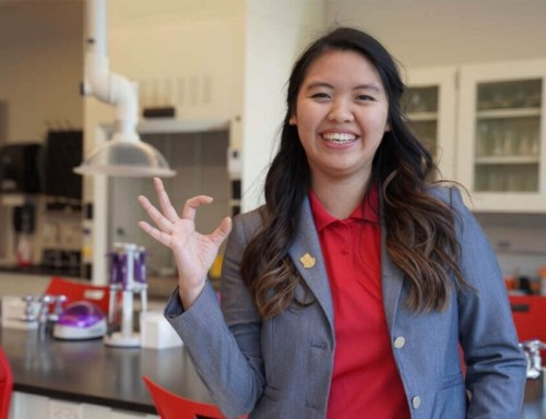 Elena Dang poses in a lab, making a C with her right hand fingers.