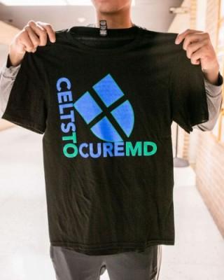 A young man holds up this year's CELTS TO CURE MD shirt. It is black with blue UST shield and says CELTS TO CURE MD in blue and green.