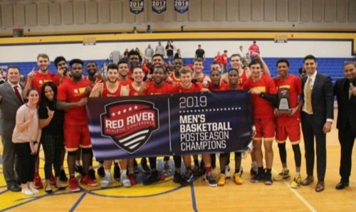 The basketball team poses for a photo holding the banner saying 2019 Men's Basketball Postseason Champions.