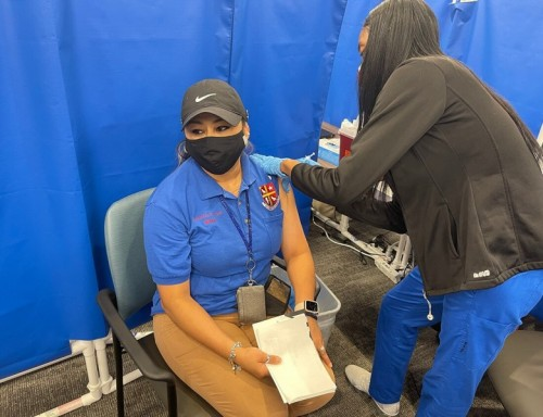 UST custodian receiving a vaccine shot
