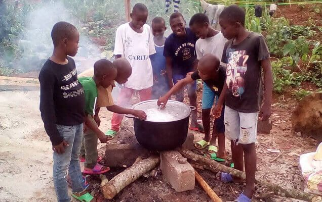 Boys cooking with a pot at orphanage in Cameroon, Africa