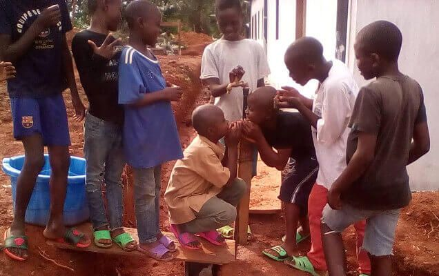 Boys drinking water from well at orphanage in Cameroon, Africa